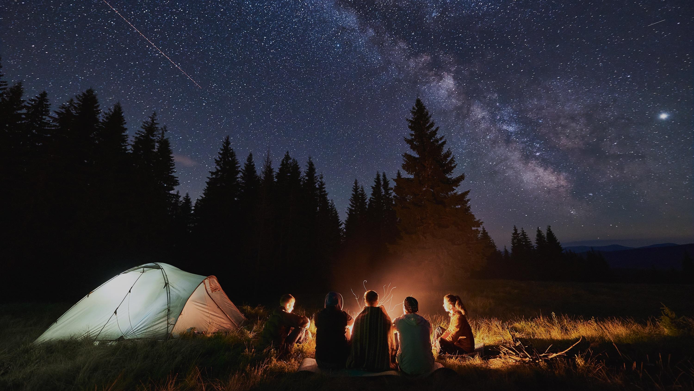 Friends Sharing Stories Around Campfire Under Milky Way | Outdoor Adventure Image