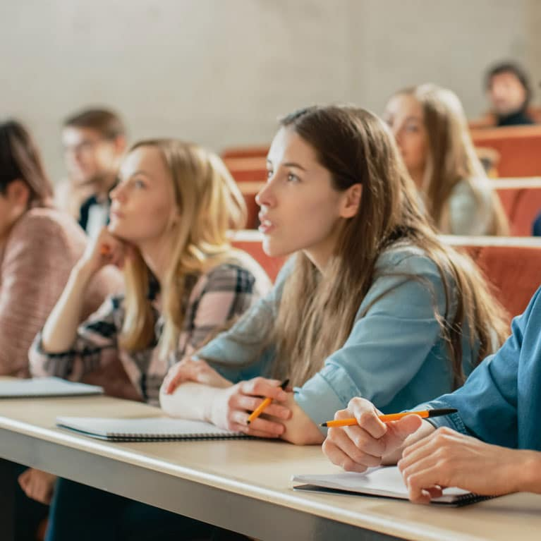 Higher Education Sector Image | Students Taking Notes in Lecture Hall
