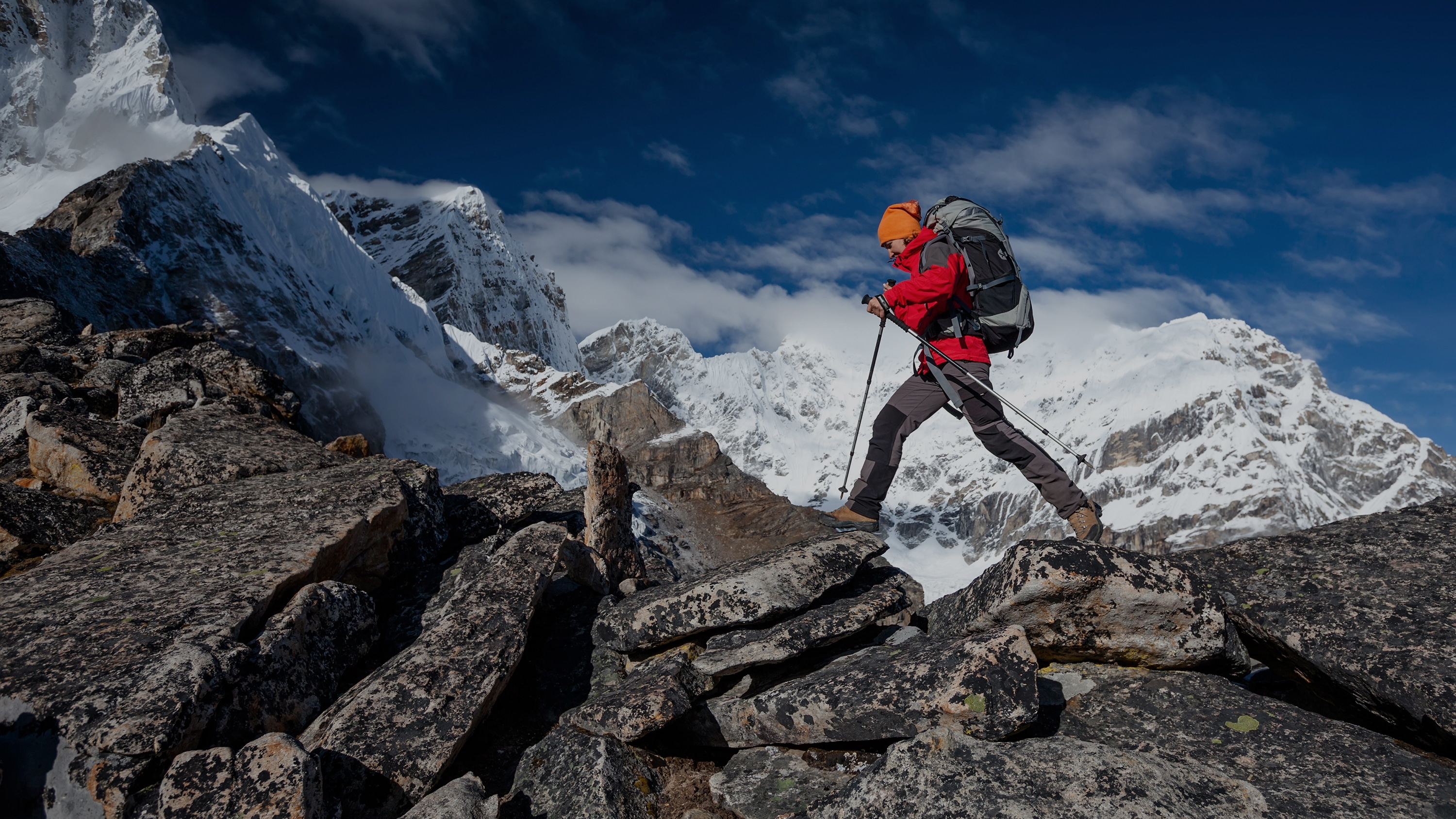 Experienced Hiker Crossing Difficult Terrain Amidst Snow-Capped Peaks | Outdoor Adventure Image