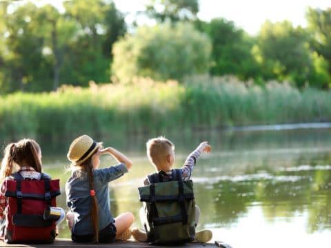 Summer Camp Kids Sitting on Dock by Lake